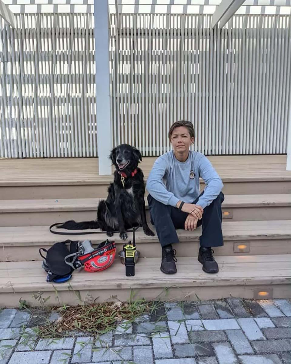 Bombera y su perro caminan entre los restos de un condominio colapsado